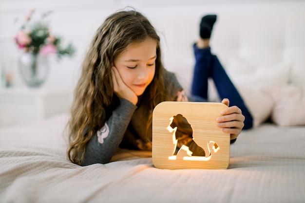 Entzückendes kleines hübsches mädchen, das auf dem bett im gemütlichen hellen raum liegt und mit hölzerner nachtlampe mit ausgeschnittenem löwenbild spielt.
