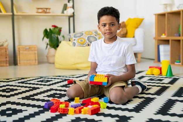 Entzückendes kleines kind afrikanischer ethnizität, das auf teppich mit schwarzweiss-dekor sitzt und freizeitspiel im wohnzimmer spielt