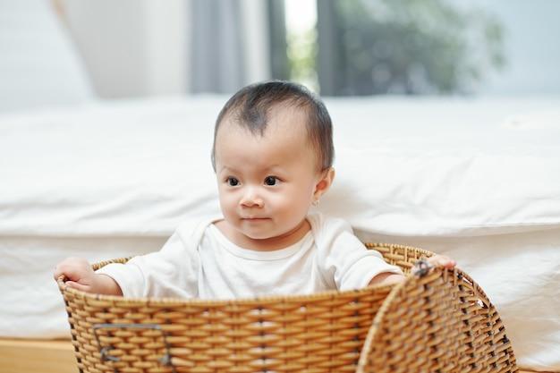 Entzückendes kleines kind, das im großen gewebten wäschekorb sitzt
