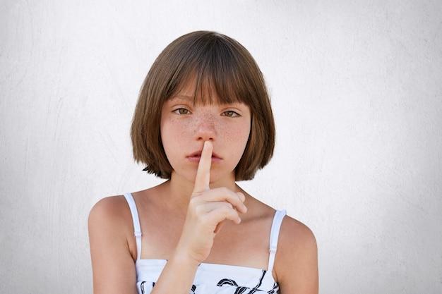Entzückendes kleines kind, das stilles zeichen zeigt und darum bittet, geräuschlos wie ihr kleines kind zu sein