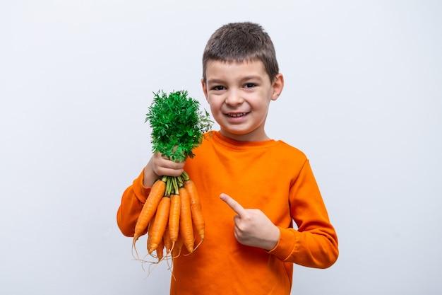 Entzückendes kleines kind mit karotten. gesundes bio-gemüse für kinder. kleiner junge, der eine karotte in seinen händen hält.