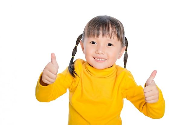 Entzückendes kleines kindermädchen, das daumen aufgibt und gesicht lokalisiert lächelt