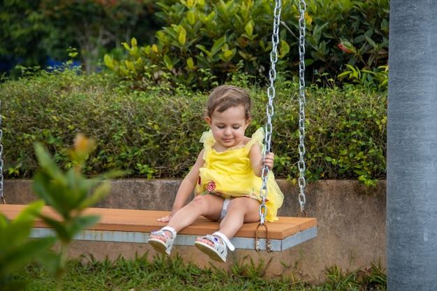 Entzückendes kleines kleinkindmädchen in einem kleid sitzt auf einer schaukel in einem tropischen park.