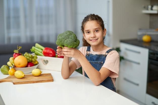 Entzückendes kleines lockiges mädchen mit jeans und t-shirt, das brokkoli hält und am tisch in der küche sitzt.