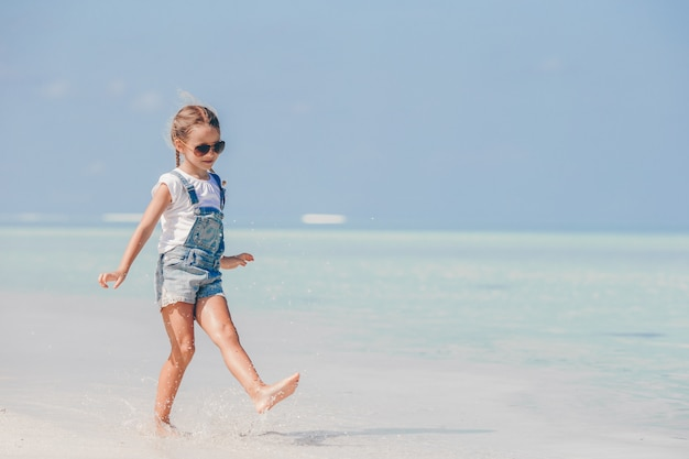 Entzückendes kleines mädchen am strand während der sommerferien