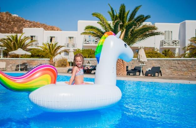 Entzückendes kleines mädchen am swimmingpool, der spaß während der sommerferien hat