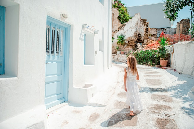 Entzückendes kleines mädchen an der alten straße des typischen griechischen traditionellen dorfs