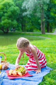 Entzückendes kleines mädchen auf dem picknick im freien nahe dem see