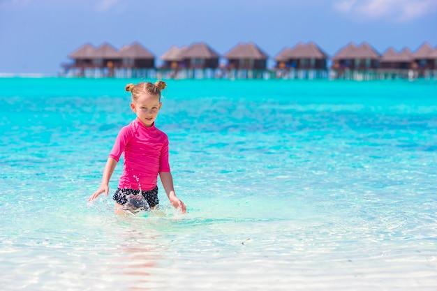 Entzückendes kleines mädchen auf dem strand während der sommerferien