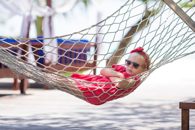 Entzückendes kleines mädchen auf den tropischen ferien, die in der hängematte sich entspannen