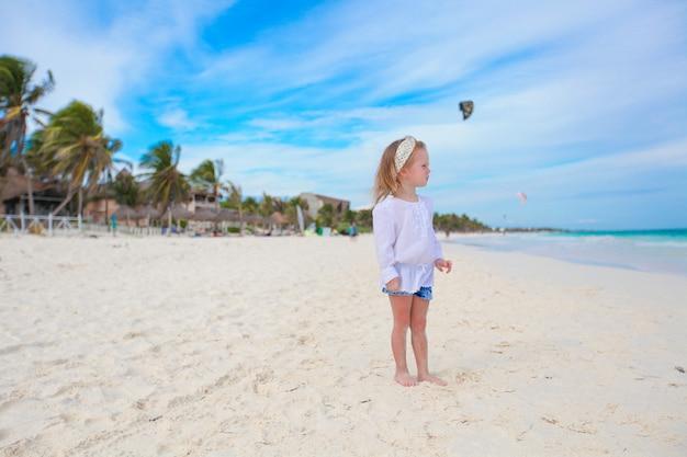 Entzückendes kleines mädchen auf weißem strand der karibik am sonnigen tag