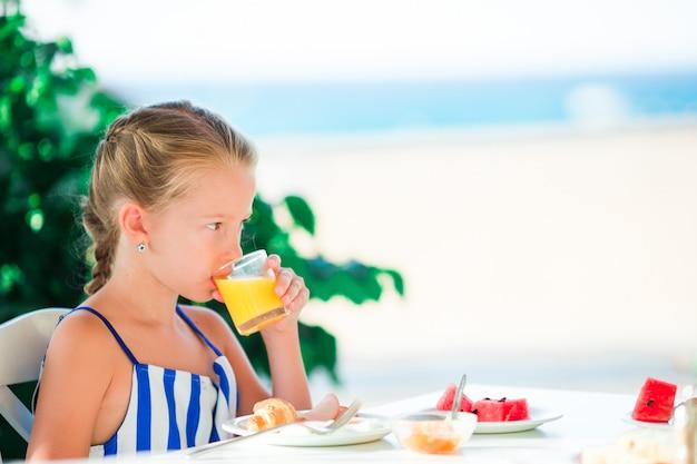 Entzückendes kleines mädchen, das am café mit seeansicht frühstückt