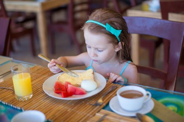 Entzückendes kleines mädchen, das am erholungsortrestaurant frühstückt