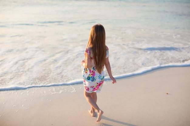 Entzückendes kleines mädchen, das am weißen tropischen strand geht