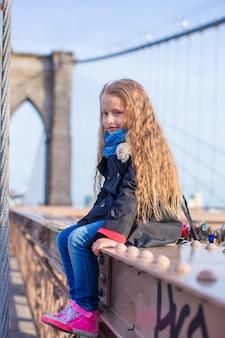 Entzückendes kleines mädchen, das an der brooklyn-brücke mit ansicht über die straße sitzt