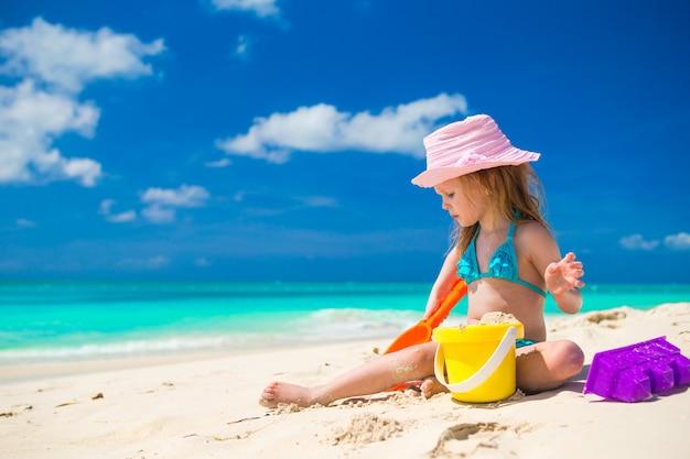 Entzückendes kleines mädchen, das auf dem strand mit weißem sand spielt