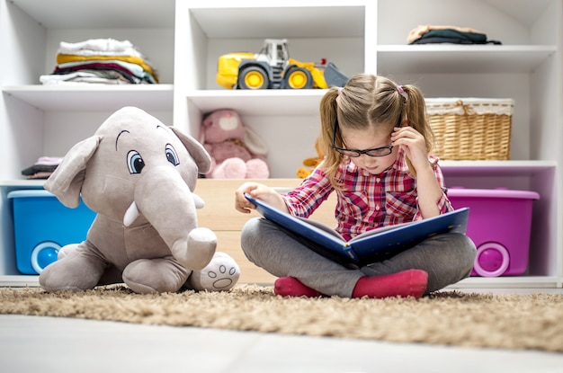 Entzückendes kleines mädchen, das auf dem teppich sitzt und ein buch für ihren ausgestopften elefanten liest