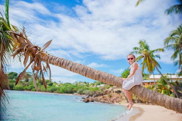 Entzückendes kleines mädchen, das auf palme während der sommerferien auf weißem strand sitzt