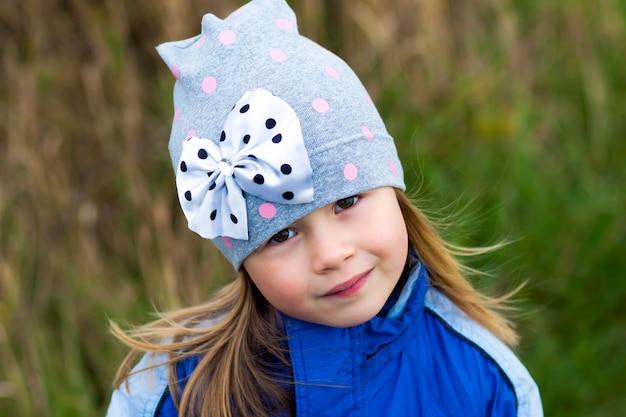 Entzückendes kleines mädchen, das auf unscharfer oberfläche aufwirft und herein zu einer kamera lächelt. wintermantel und hut tragen. reizendes junges mädchen im herbst draußen.