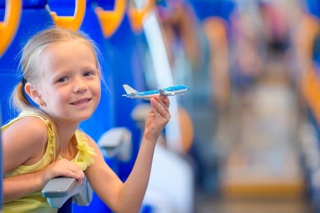 Entzückendes kleines mädchen, das auf zug reist und spaß mit flugzeugmodell in den händen hat