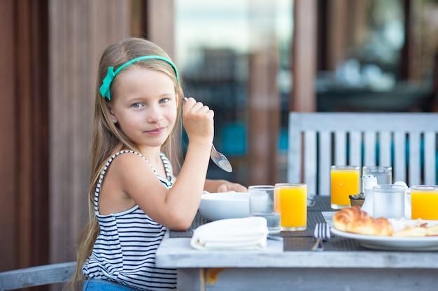 Entzückendes kleines mädchen, das café am im freien frühstückt