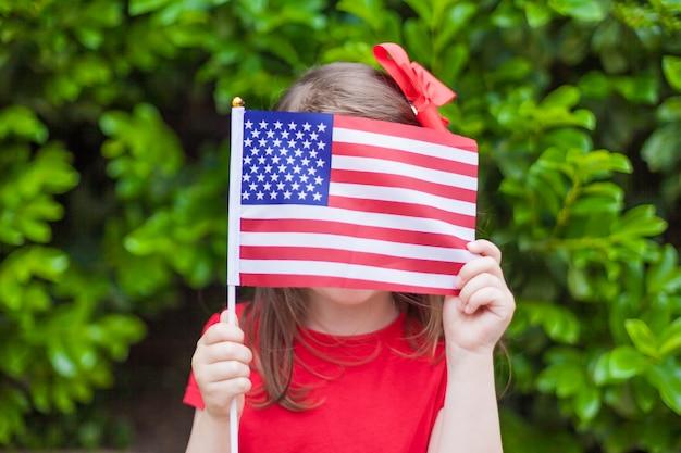 Entzückendes kleines mädchen, das draußen amerikanische flagge am schönen sommertag hält