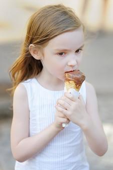 Entzückendes kleines mädchen, das draußen eiscreme am sommer isst
