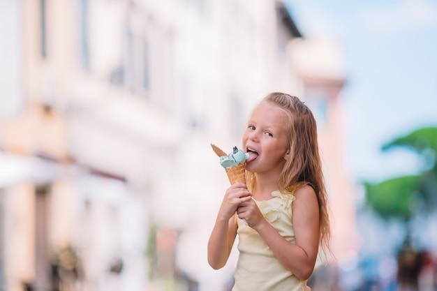 Entzückendes kleines mädchen, das draußen eiscreme am sommer isst.