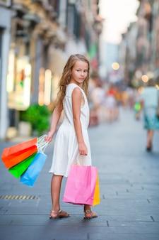 Entzückendes kleines mädchen, das draußen mit einkaufstaschen in rom geht.