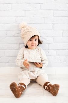 Entzückendes kleines mädchen, das ein telefon hält