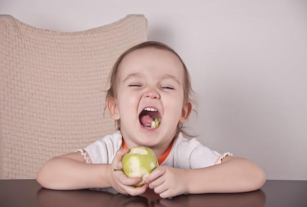 Entzückendes kleines mädchen, das einen grünen apfel isst