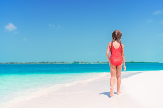 Entzückendes kleines mädchen, das entlang karibischen strand des weißen sandes geht