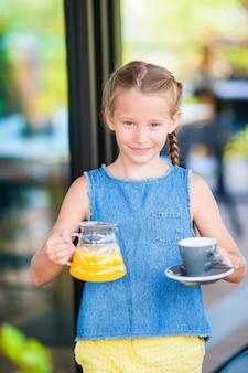 Entzückendes kleines mädchen, das früh am morgen am café frühstückt