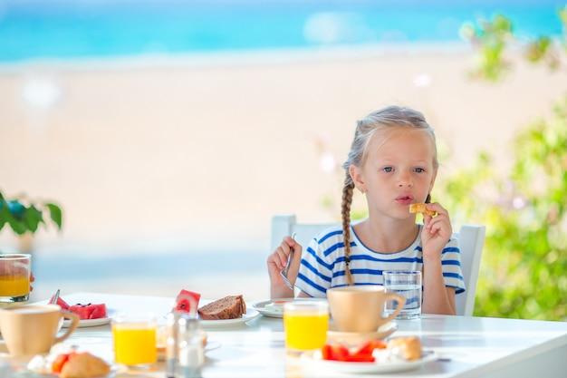 Entzückendes kleines mädchen, das früh am morgen am café mit seeansicht frühstückt