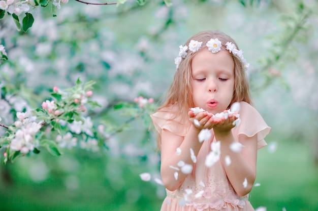 Entzückendes kleines mädchen, das frühlingstag in blühendem garten des apfels genießt