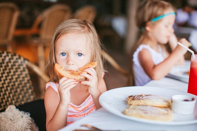 Entzückendes kleines mädchen, das frühstück im straßencafé hat