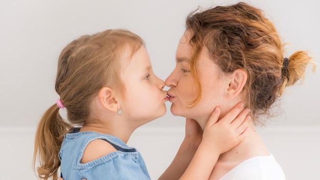 Entzückendes kleines mädchen, das ihre mutter küsst