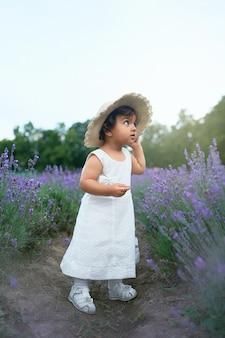 Entzückendes kleines mädchen, das im lavendelfeld aufwirft