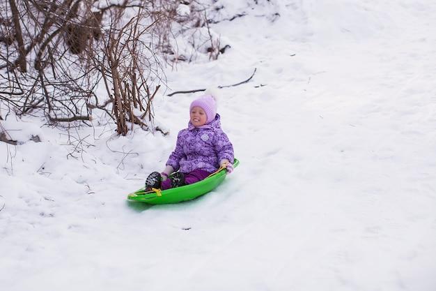 Entzückendes kleines mädchen, das im schneebedeckten wald rodelt
