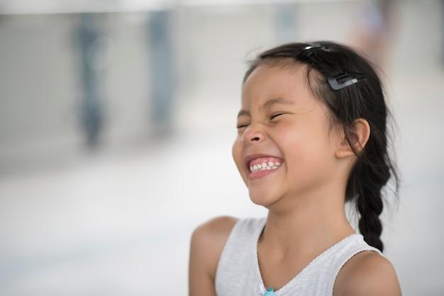 Entzückendes kleines mädchen, das in der straße lacht