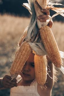Entzückendes kleines mädchen, das in einem maisfeld am schönen herbsttag spielt. hübsches kind, das einen maiskolben hält. mit kindern ernten. herbstaktivitäten für kinder.