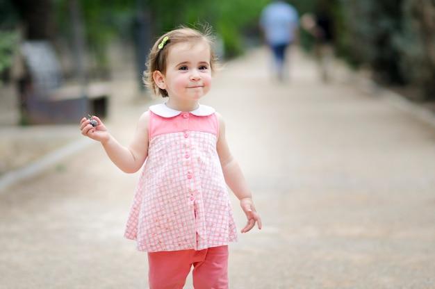 Entzückendes kleines mädchen, das in einem städtischen park spielt
