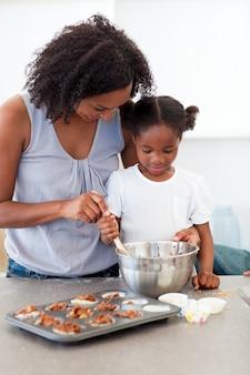 Entzückendes kleines mädchen, das kekse mit ihrer mutter vorbereitet