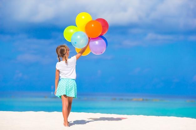 Entzückendes kleines mädchen, das mit ballonen am strand spielt