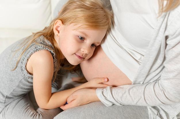 Entzückendes kleines mädchen, das mit dem schwangeren mutterbauch spielt