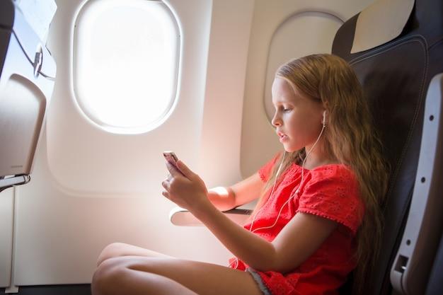 Entzückendes kleines mädchen, das mit einem flugzeug reist. hörende musik des kindes, die nahe flugzeugfenster sitzt