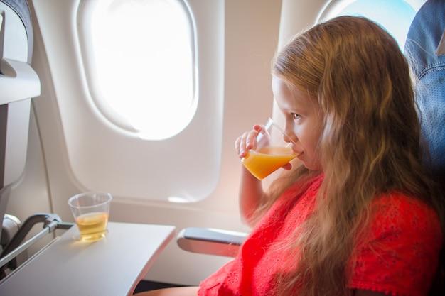 Entzückendes kleines mädchen, das mit einem flugzeug reist. kind, das den orangensaft sitzt nahe flugzeugfenster trinkt