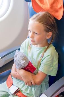 Entzückendes kleines mädchen, das mit einem flugzeug reist. kind, das nahe flugzeugfenster sitzt