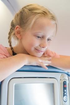 Entzückendes kleines mädchen, das mit einem flugzeug und einem lächeln reist