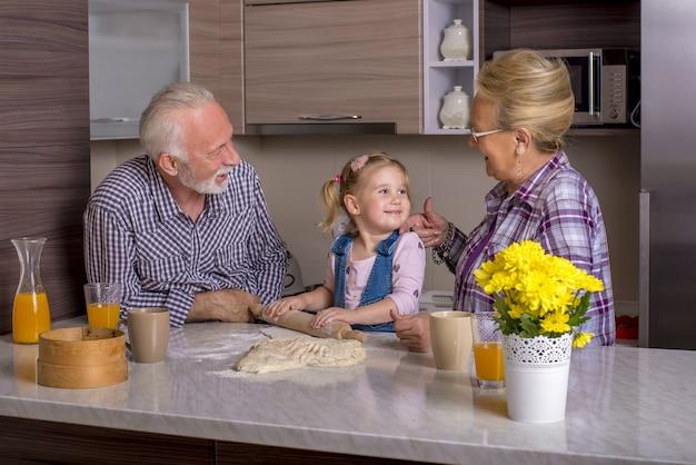 Entzückendes kleines mädchen, das mit ihren großeltern kocht